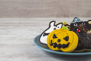 Different home made halloween cookies in a plate on white wooden table.