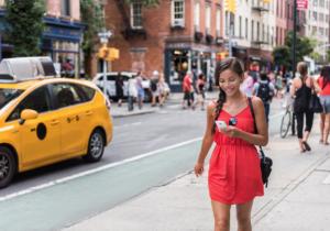 Women wearing a red dress walking down a city street