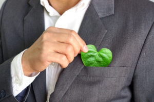 Man pulling a heart shaped leaf from his suite pocket