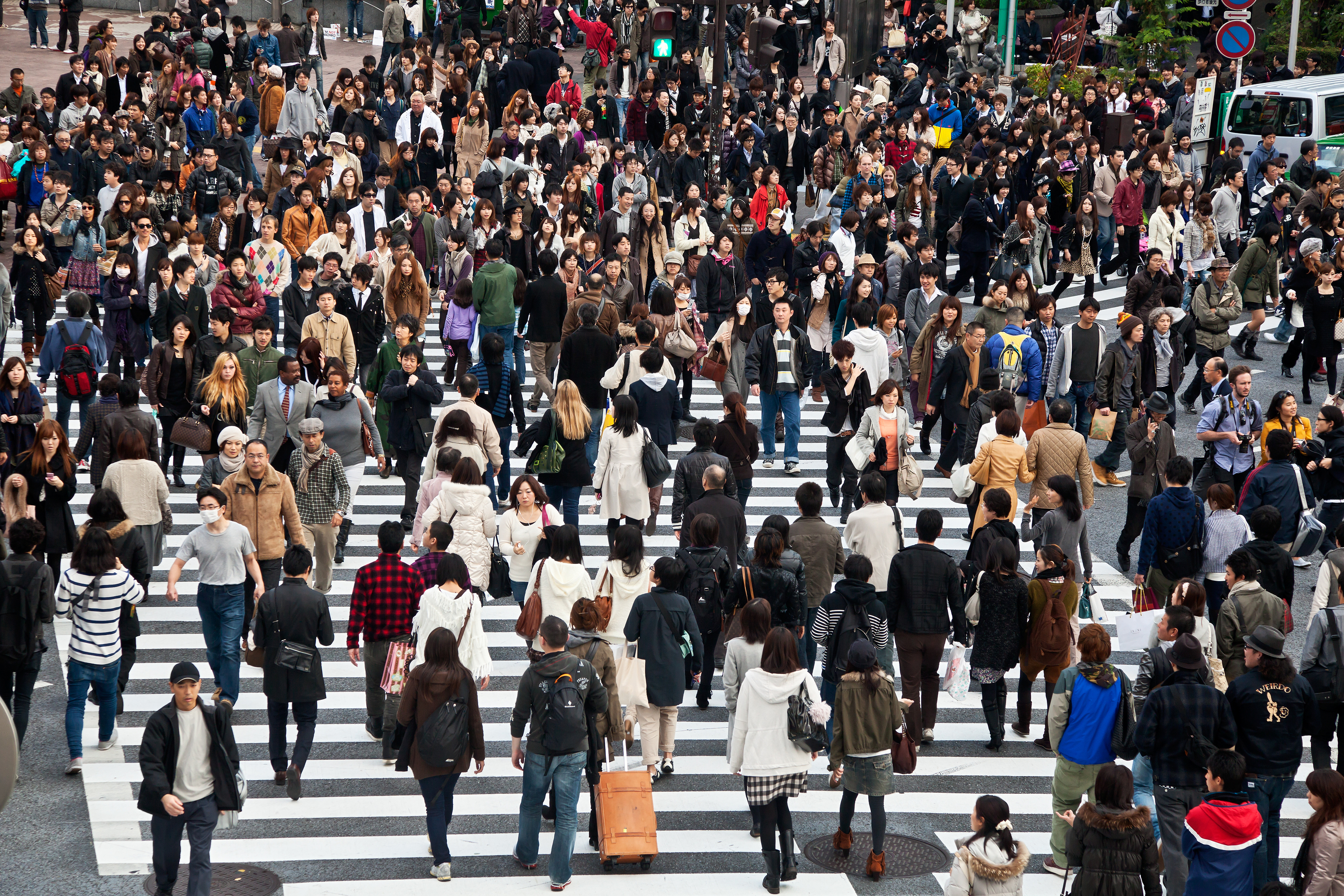 Crowd of people walking across the street