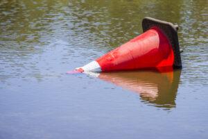 Roadside cone laying in water