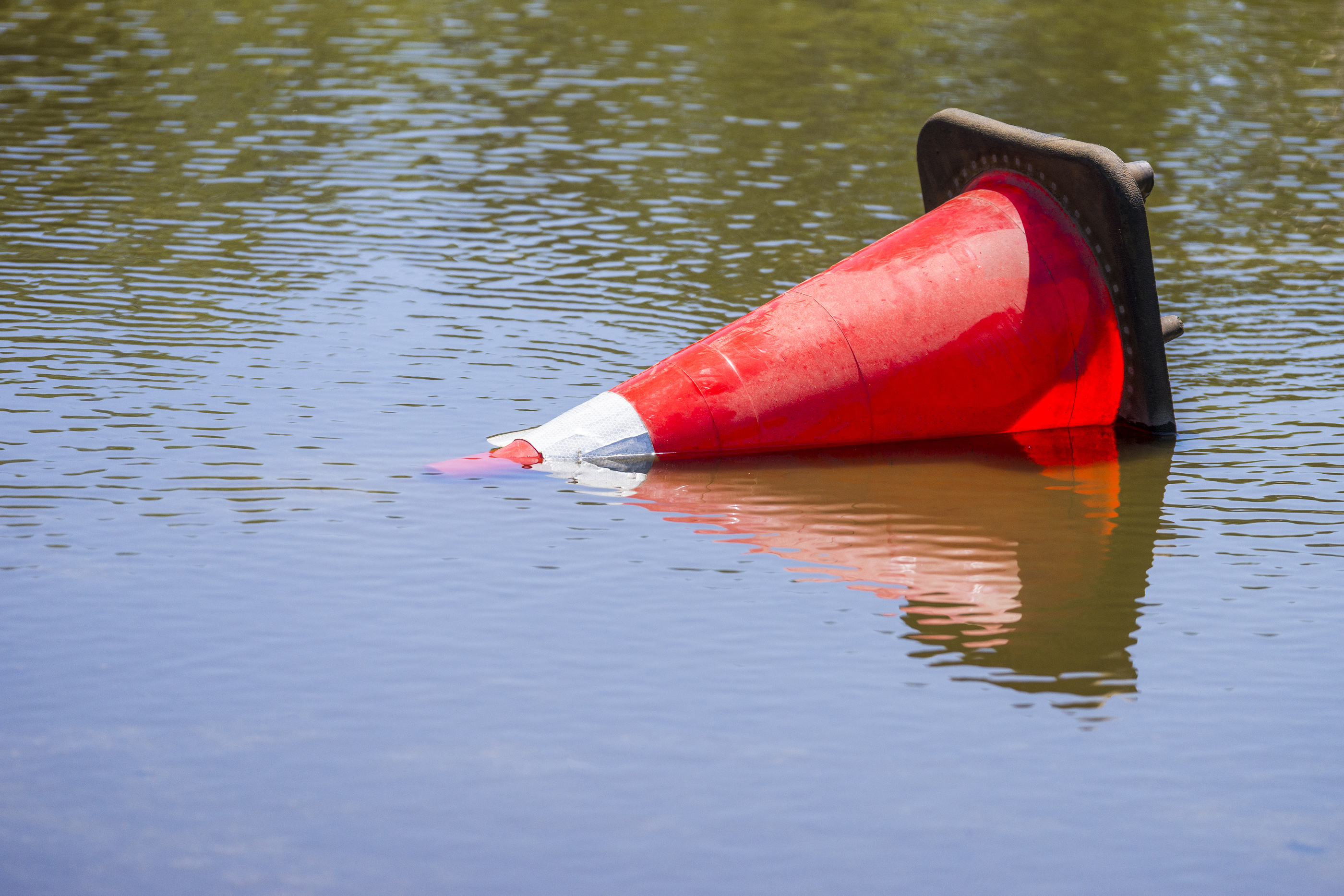 Roadside cone laying in water