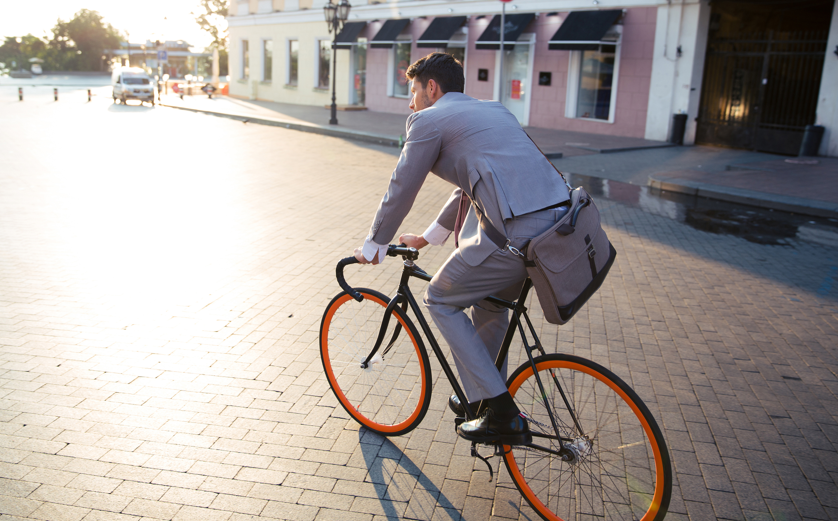Caucasian man wearing a grey suite riding a black bicycle