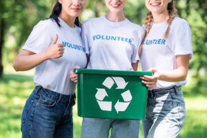 Three women wearing volunteering t-shirts and a green recycle bin